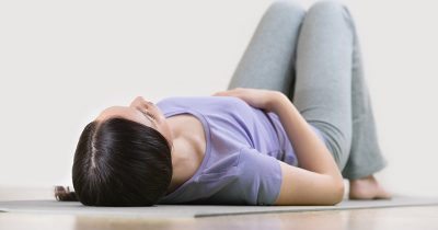 Woman lying on her back practising Body Awareness exercise