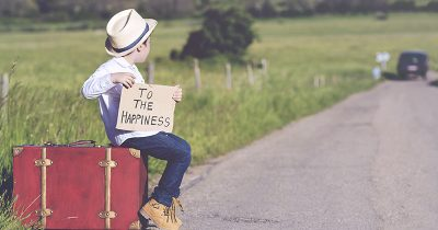 Boy at the Side of the Road with a Sign with the Words 'To the Happiness' Written on it