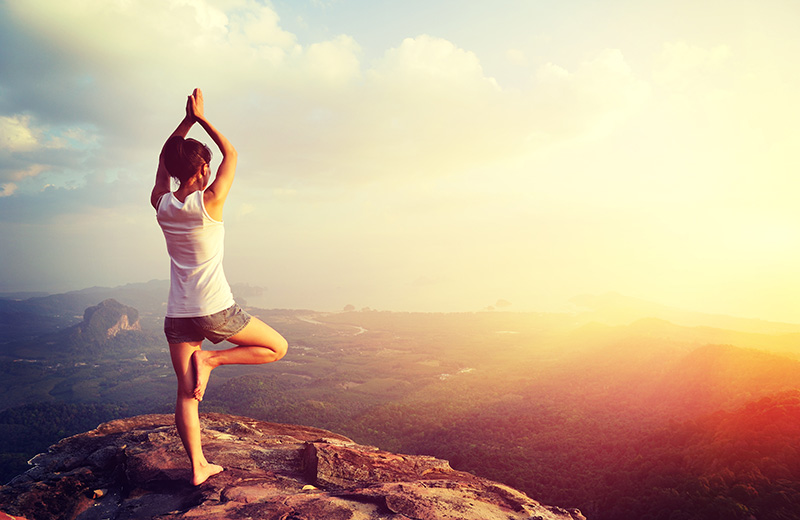 Yoga woman meditation on mountain peak