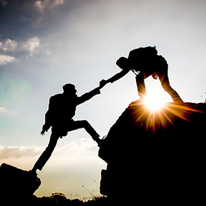 One Man Offering A Hand to Another to Climb Over a Gap on a Mountain, Image is in Silhouette