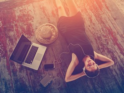 Woman using mental health apps to relax - lying on a wooden floor with her eyes closed and headphones on