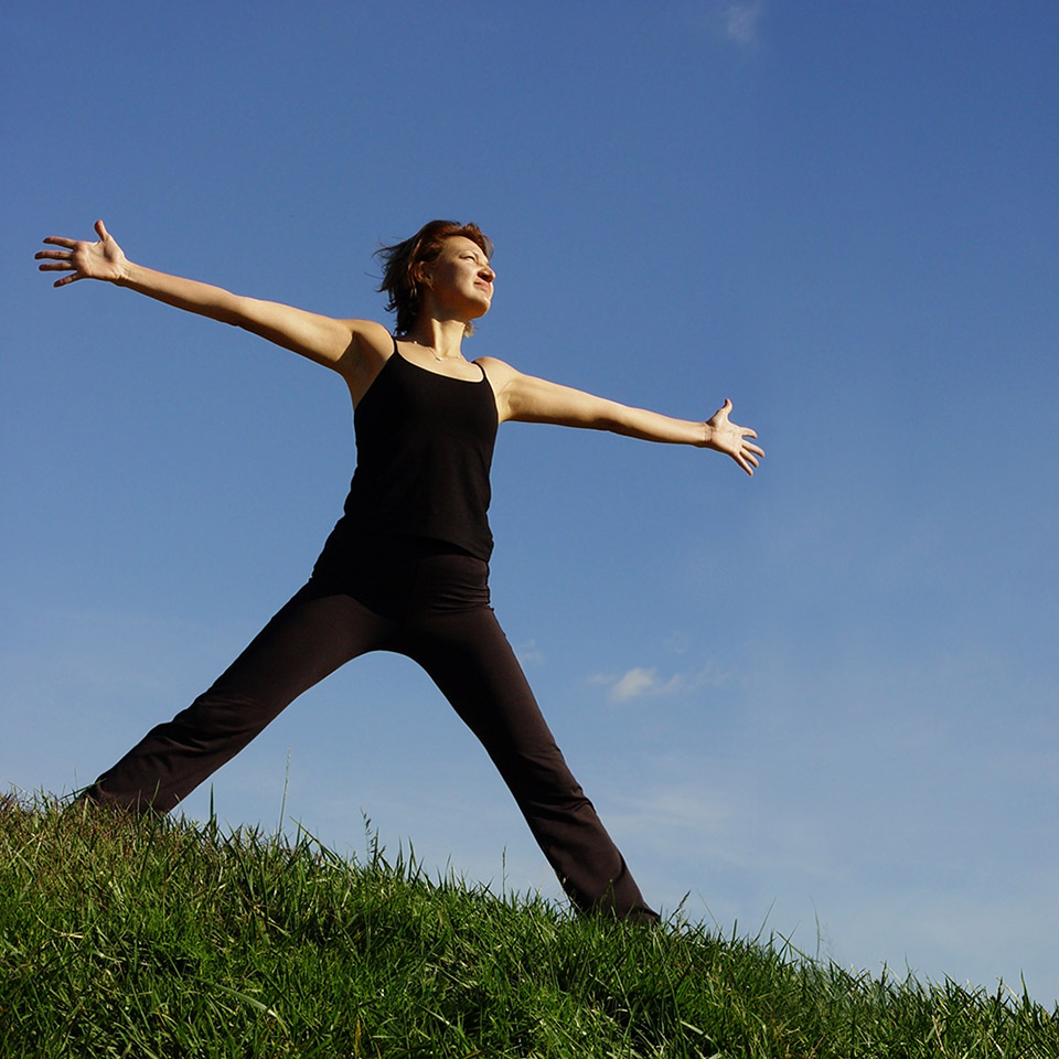 Woman on to of a hill with arms stretched out wide