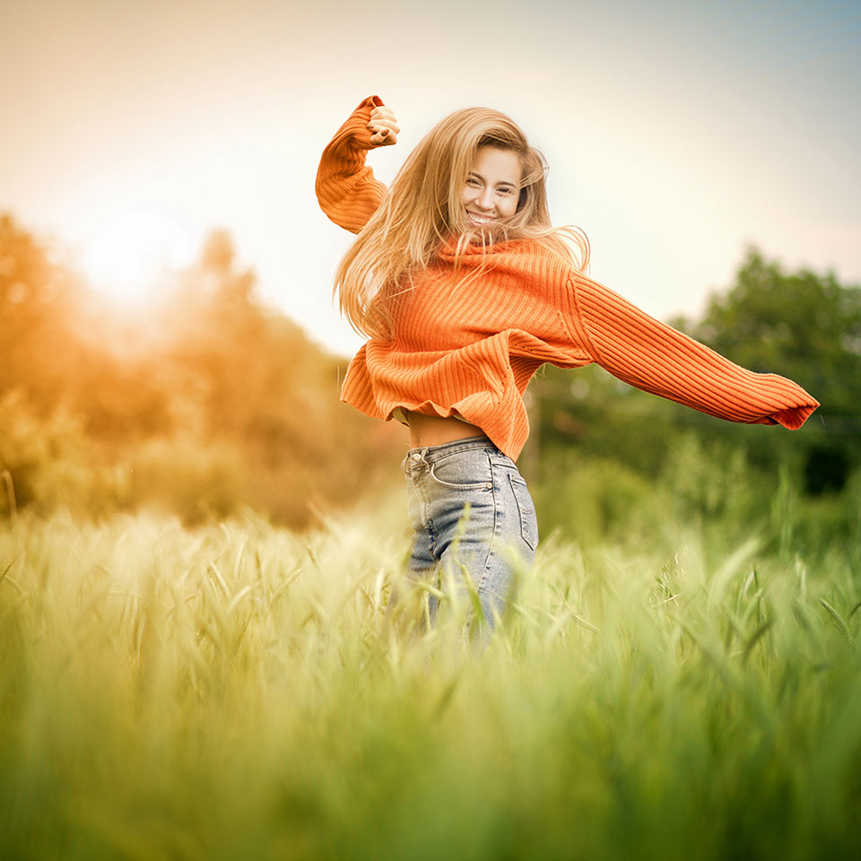 Happy woman jumping in field