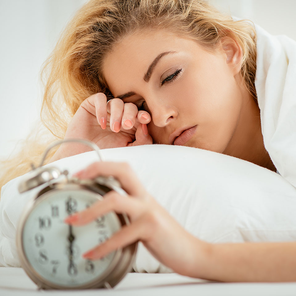 Woman in bed, looking tired, turning alarm clock off