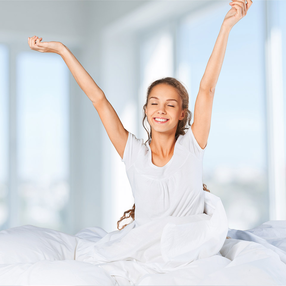 Woman sitting up in bed stretching and smiling - refreshed after a good night's sleep