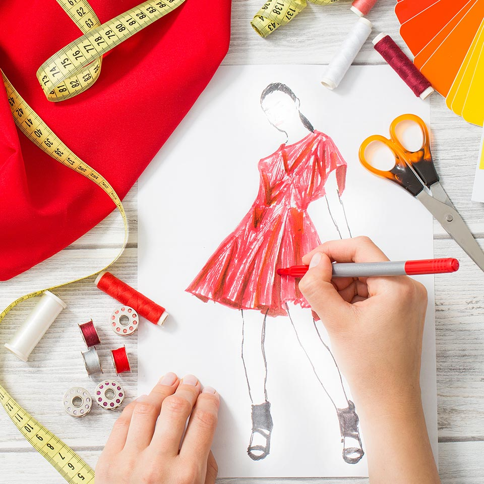 Fashion designer's hands working on a dress illustration at a table surrounded by sewing eqiupment
