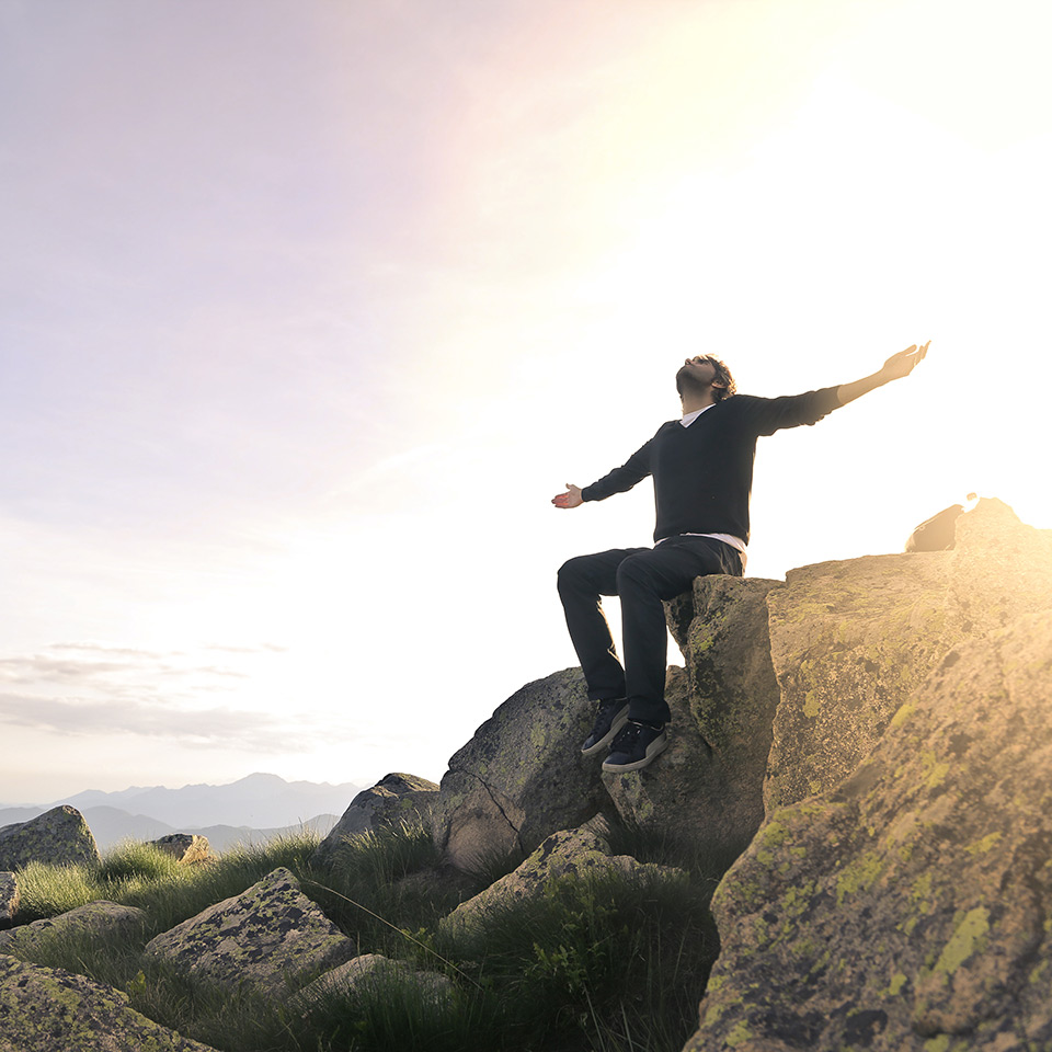 Man feeling free of anger, sitting on top of a mountain with the sun rising behind his back