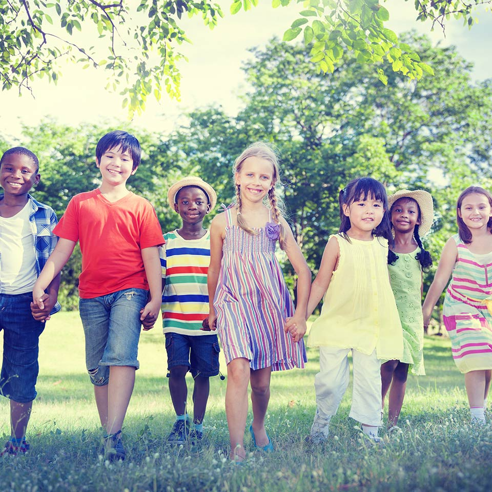 Mixed group of happy children holding hands in the park