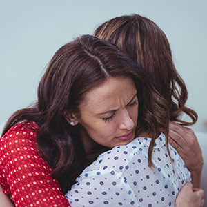 Woman hugging another woman, showing the physical effect of online counselling