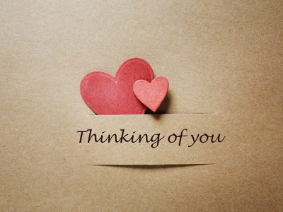 Relationship philosophy - Paper hearts on a brown paper background with the words 'Thinig of you' written below them
