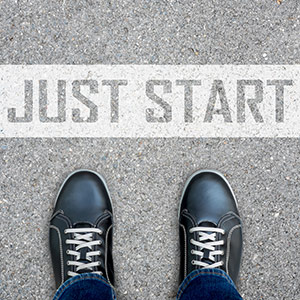 Starting a Blog - 'Just Start' written on the floor, in front of someone's feet