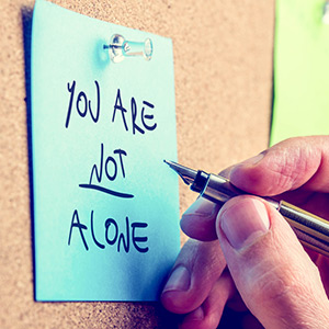 Writing a Blog - Post-it note displaying the words 'You are not alone'