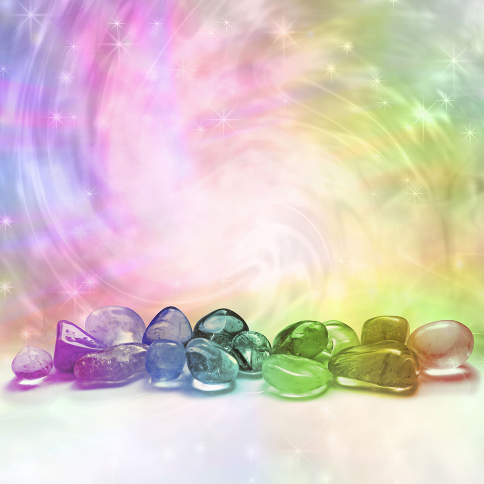 Advanced Crystal Healing - Various colourful crystals in front of a colourful, swirling vortex of light