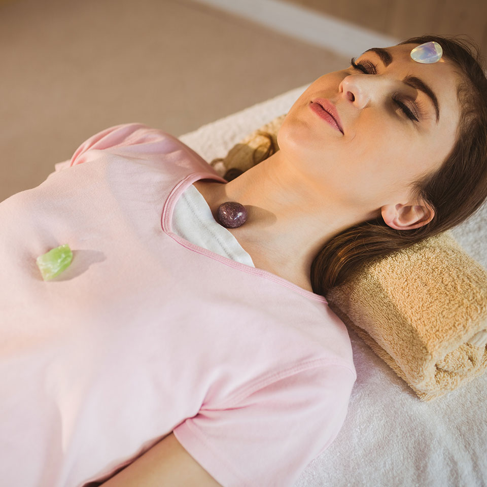 Advanced Crystal Healing - Woman lying down with crystals on chakra points as she receives crystal healing