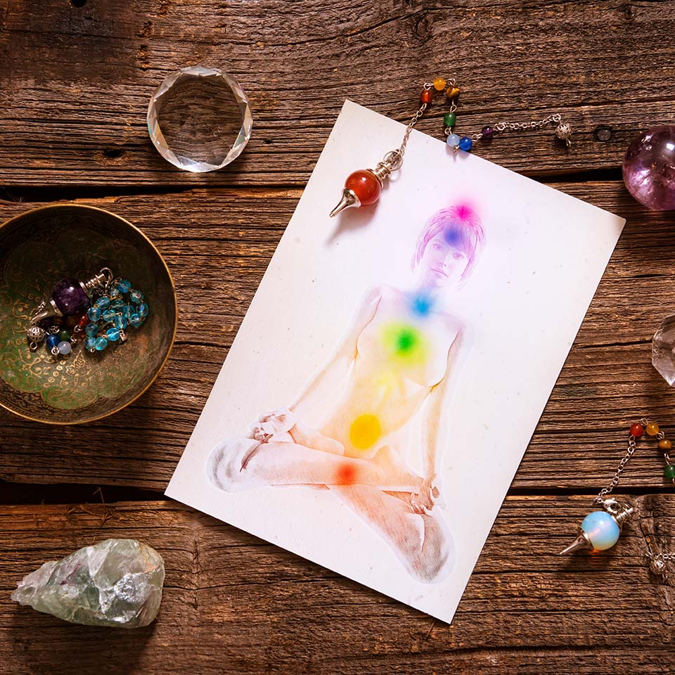 A desk with various chakra and aura healing tools, such as healing stones, pendants, and a diagram of the positions and colours of the chakras