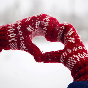 Knitted gloves making a heart sign in a snowy scene