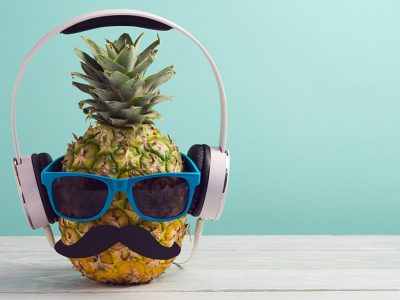 Pineapple dresses with a moustache and sunglasses listening to food podcasts through headphones