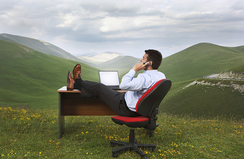 Reduce Stress: Business man feeling relaxed at his desk on a green hill surrounded by mountains.jpeg