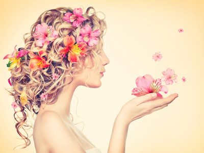 Hair Care Tips: Woman with flowers in her hair blowing flowers cupped in the hands