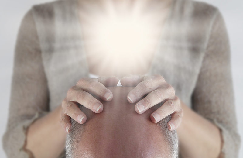 Man receiving Reiki Attunement from Master Reiki Practitioner