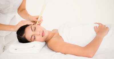 Woman receiving ear candling treatment at a spa