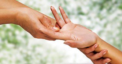 Client receiving hand reflexology treatment