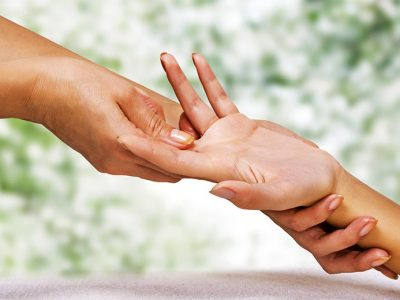 Client receiving hand reflexology treatment