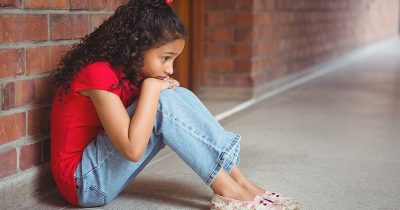 Young girl sat on the floor at school, feeling sad after dealing with a bully