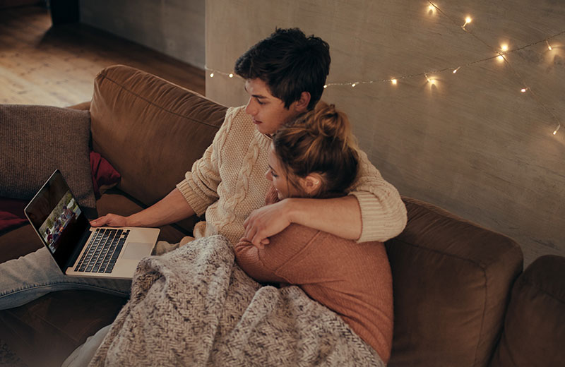An example of hygge - a couple in knitwear cuddle up together under a blanket, watching a film