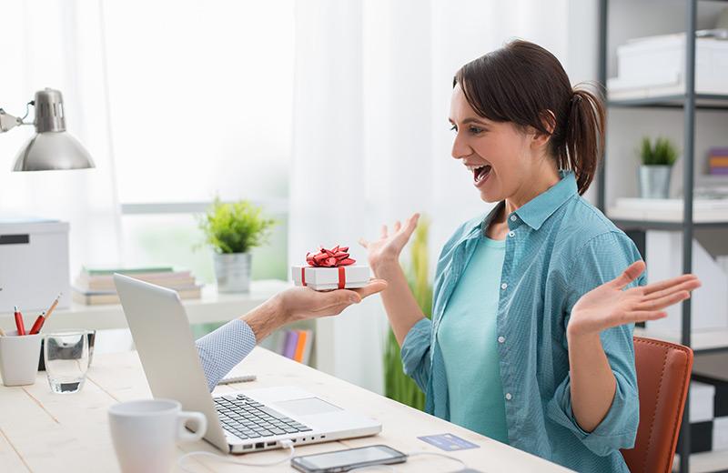 Woman receiving a gift through a laptop