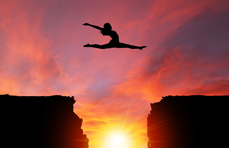 Metaphor for leaping into the new year - silhouette of a woman leaping from one cliff to another