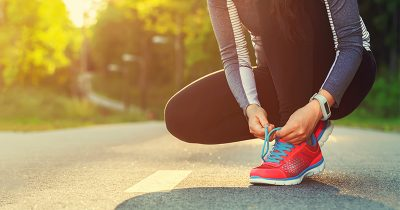 Woman tying the laces of her trainers before going running