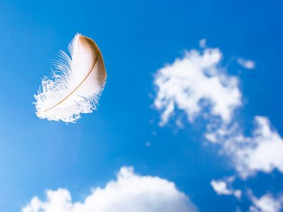 A feather floating in a blue sky with clouds floating in the background - a sign of an angel messenger