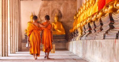Two young followers of Buddhism walking through the a Buddhist temple