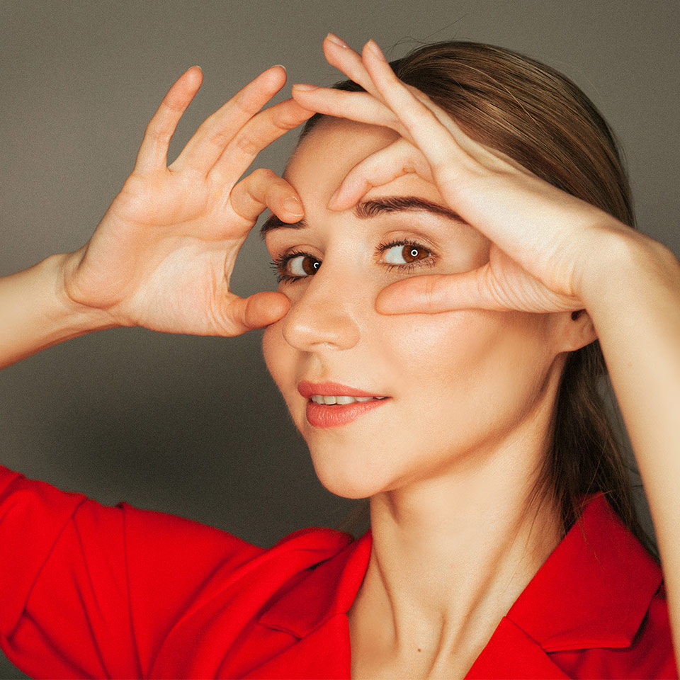 Woman looks at camera whilst doing face yoga