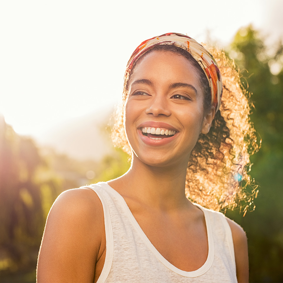 Smiling woman lit by the sun outdoors
