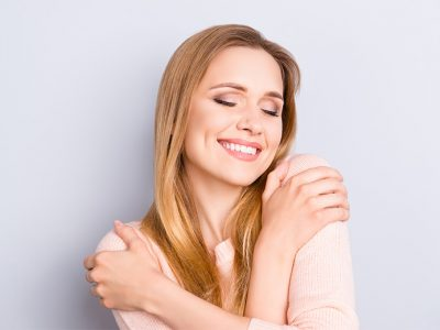 Smiling woman giving herself a hug