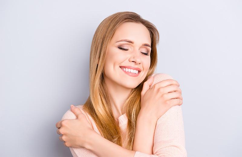 Smiling woman giving herself a hug