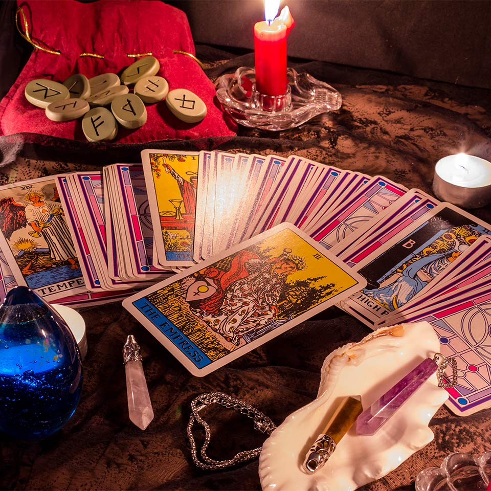 Fortune teller female hands and tarot cards on wooden table.