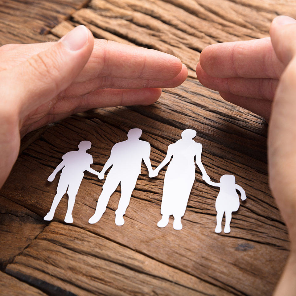 Hands protectively covering a paper cutout of a family on a wooden table