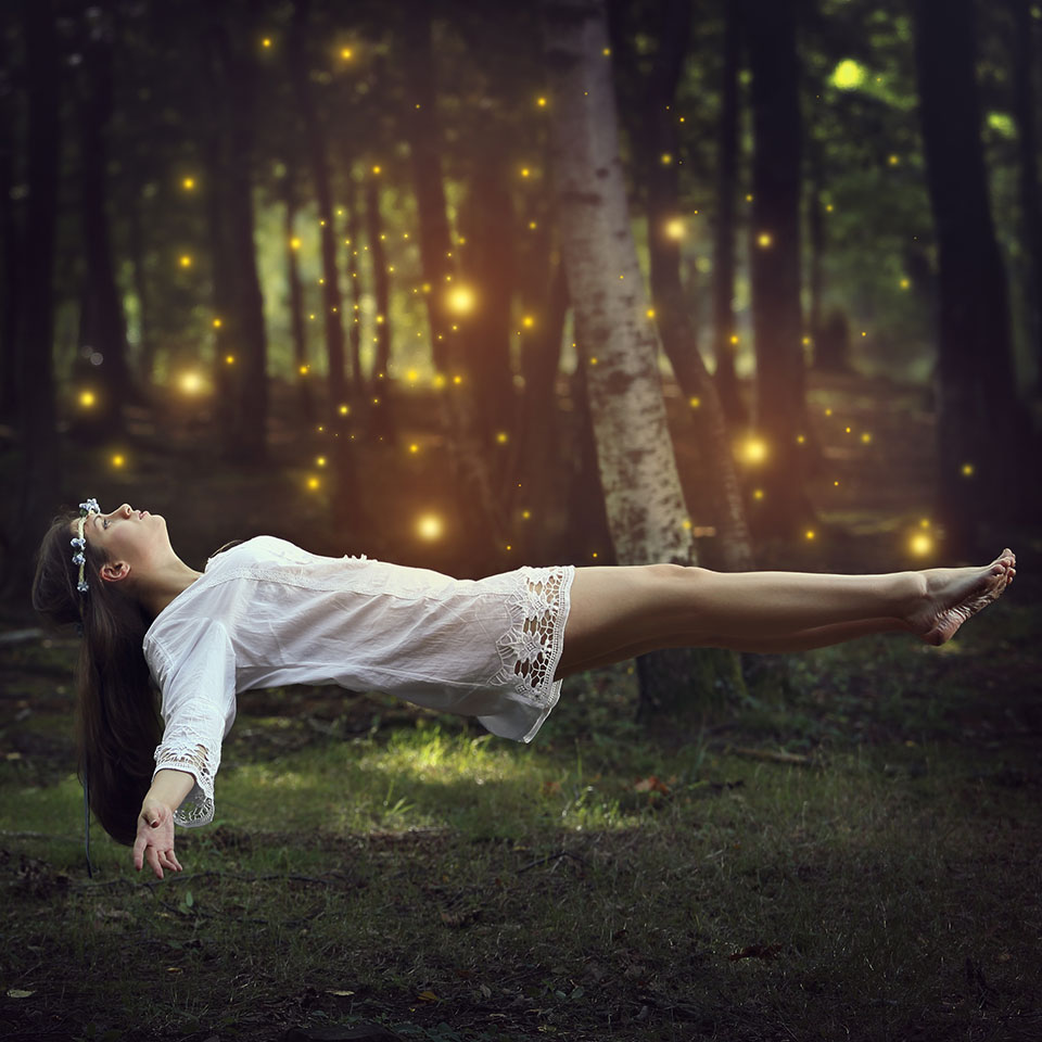 A woman lying down but floating above the ground in a forest of trees and glowing lights