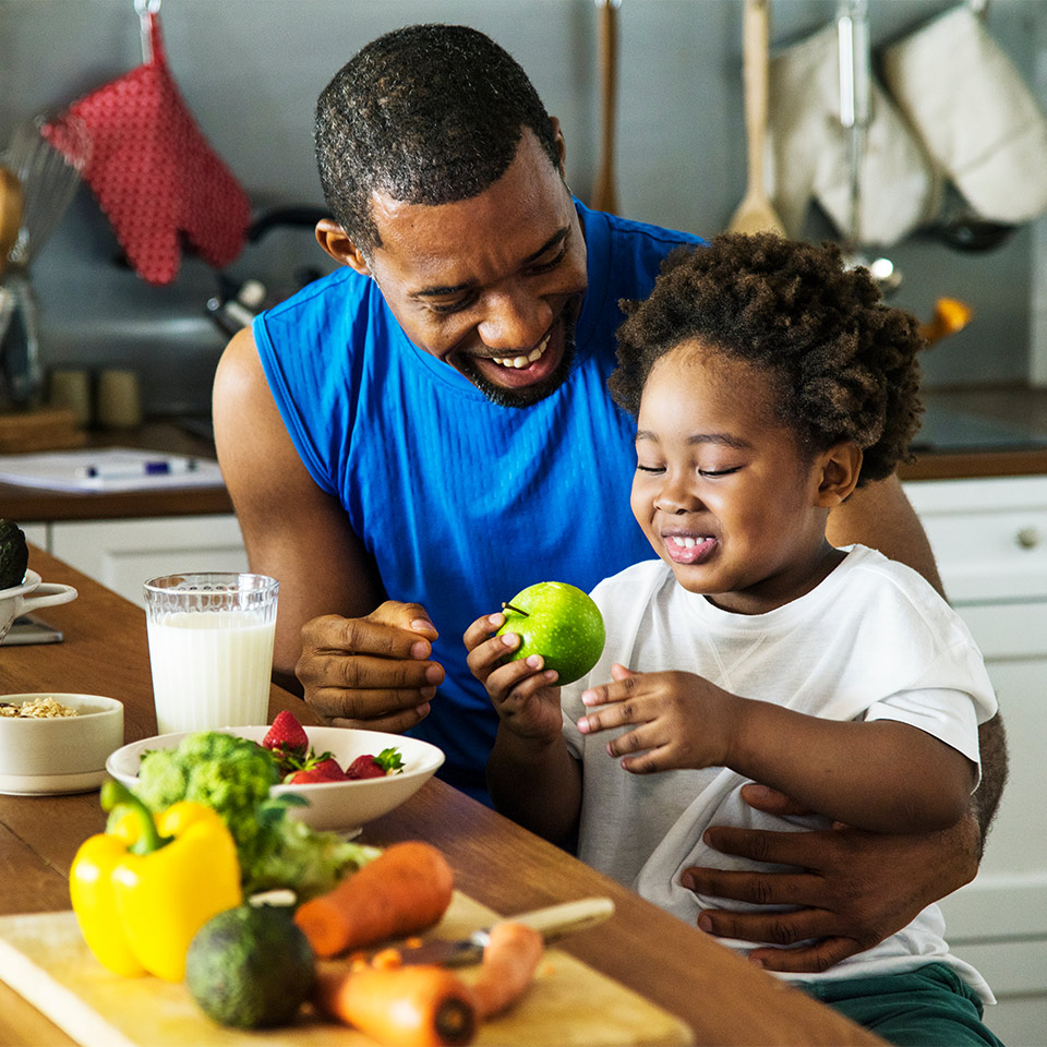 A father and son in their kitchen enjoying healthy fruit and vegetables