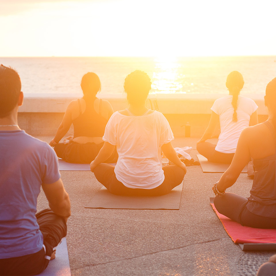 Group of people sitting and meditating outside at sunset