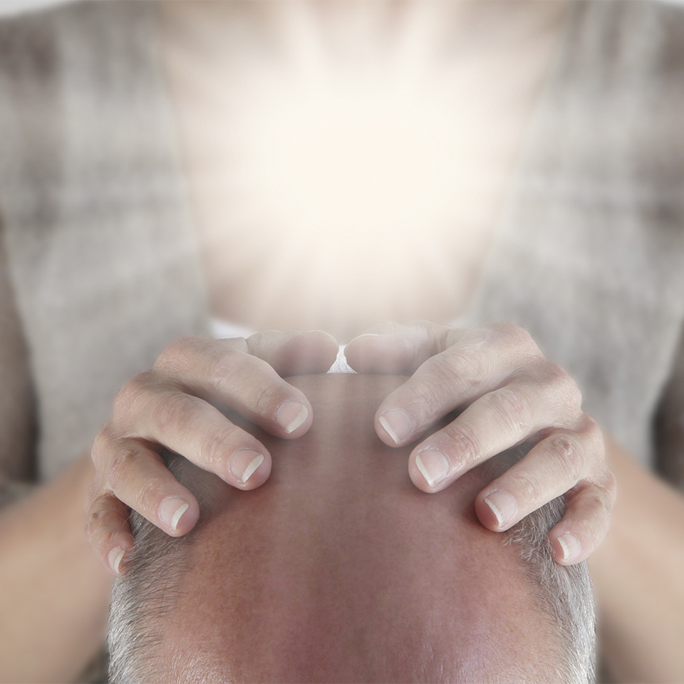 Male patient having their crown chakra opened ready for healing energy to be channeled by practitioner