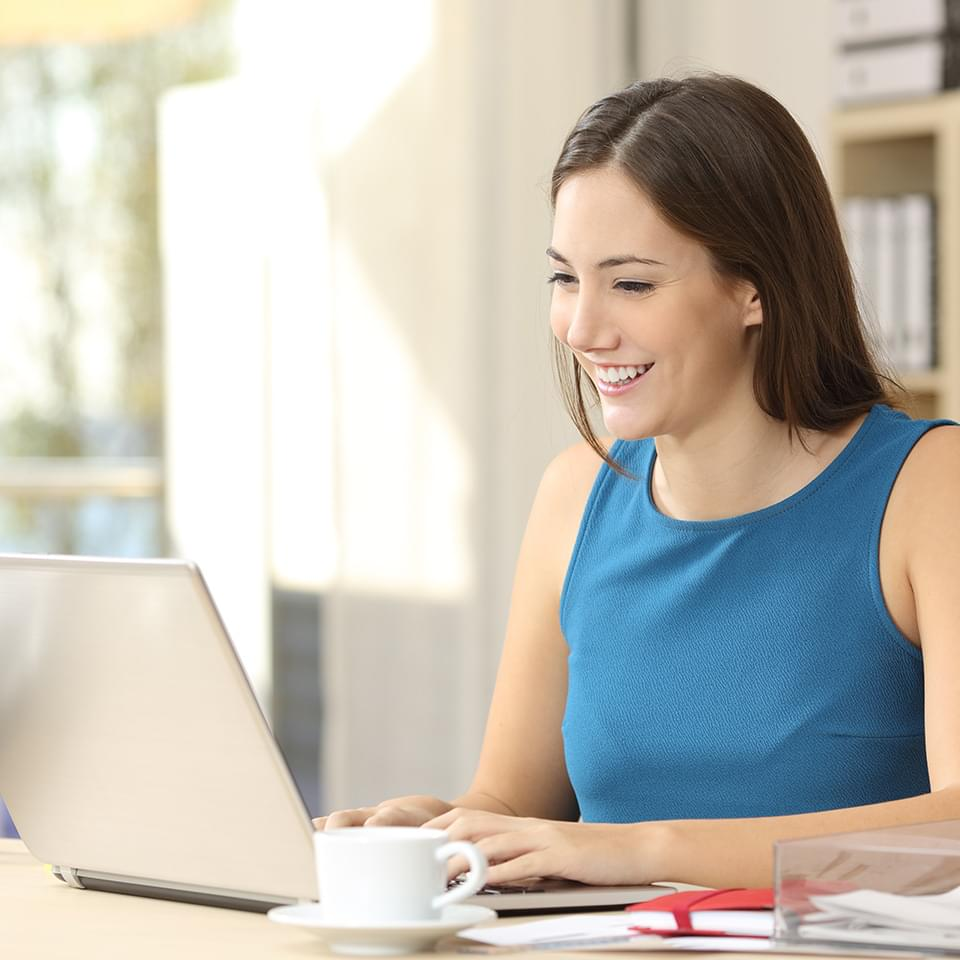 Smiling woman at laptop studying an ILM-approved course with Centre of Excellence