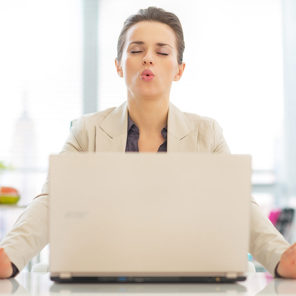 Business woman using breathing technique from the Anger and Aggression Management Practitioner Course to calm her mind