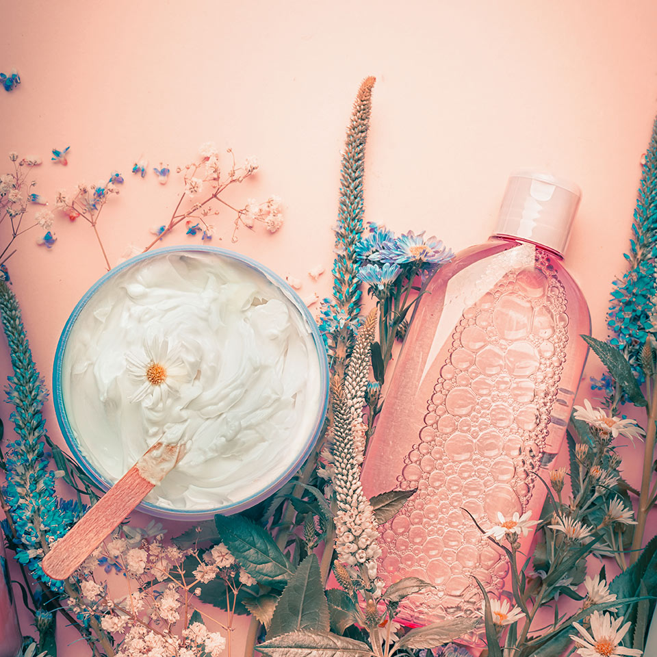 Herbal cream and lotion skincare products and flowers on a pastel background