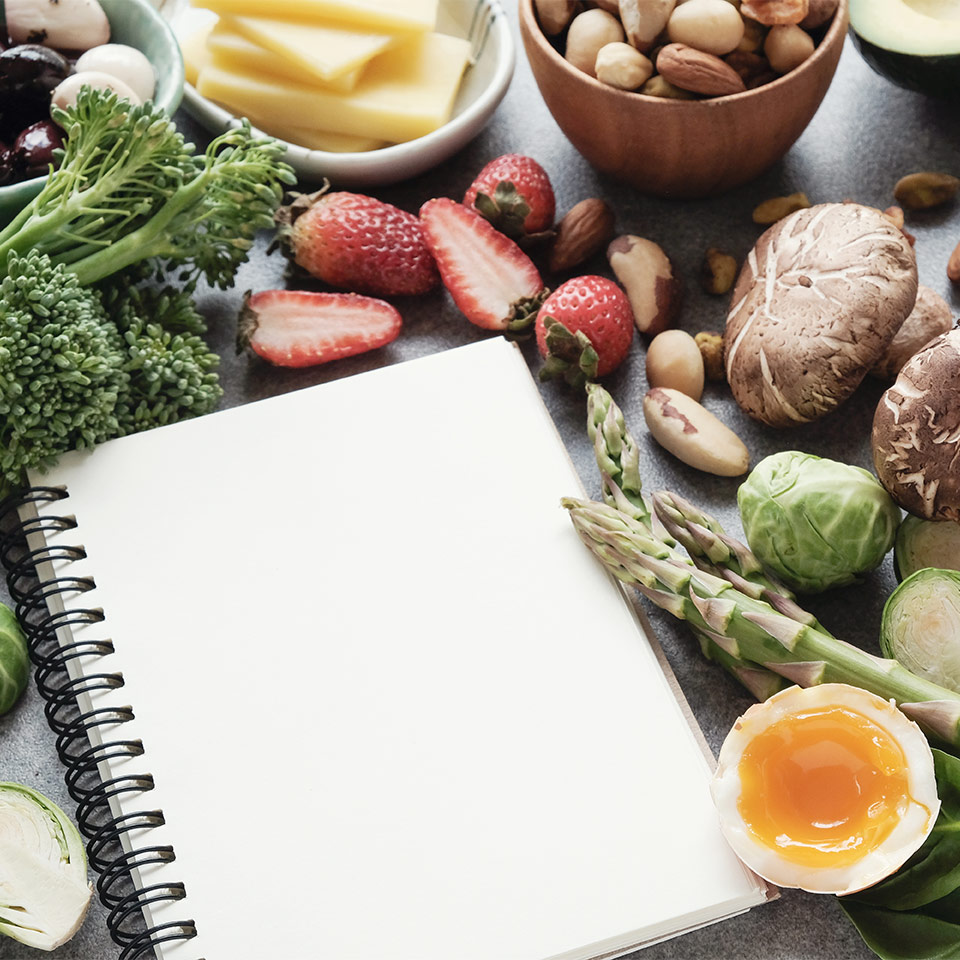 Healthy, Ketogenic diet ingredients on a table, alongside a blank pad, ready for meal planning