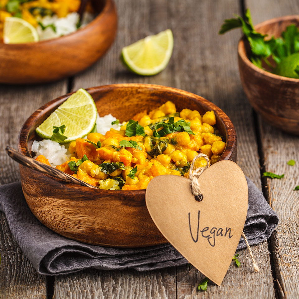 Vegan curry in wooden bowl on a wooden background