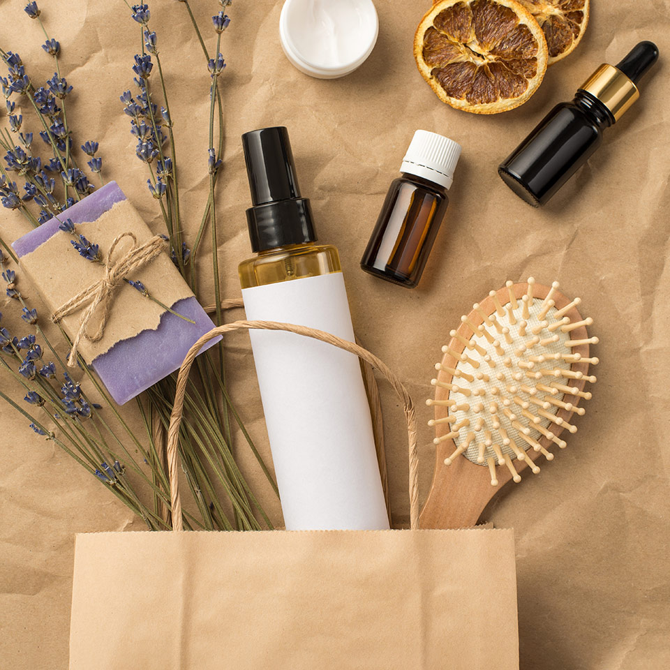 Top view photo of organic haircare products and springs of lavender in a paper bag